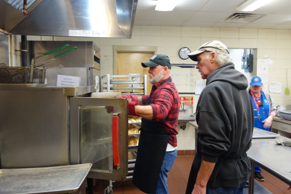 Loaves and Fishes volunteer Ken with cook Richard observing and Mary Thomas manager 1.30.19